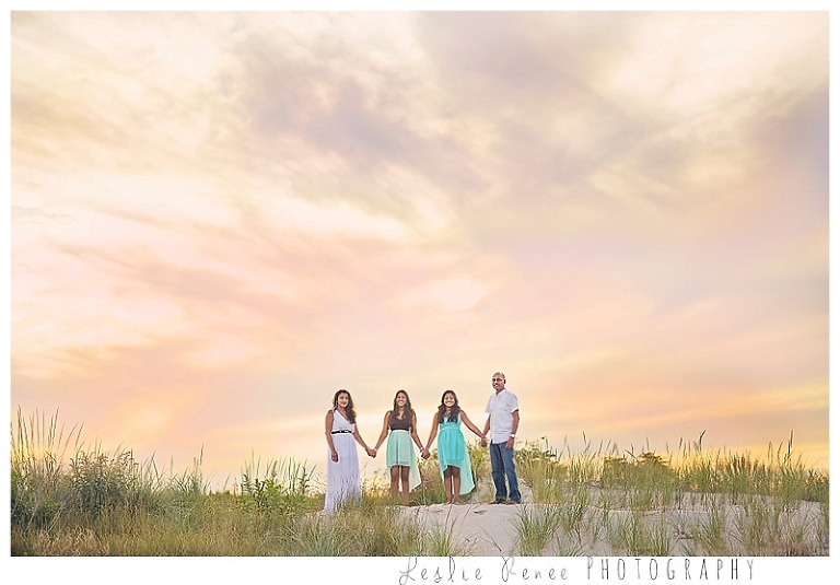 family of four with beautiful colorful sky