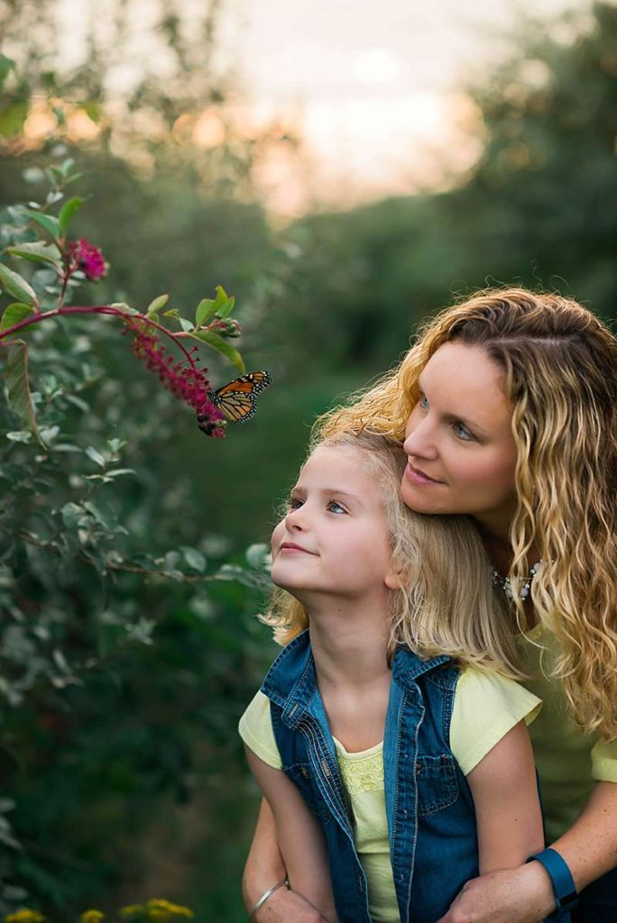 mom and daughter see butterfly